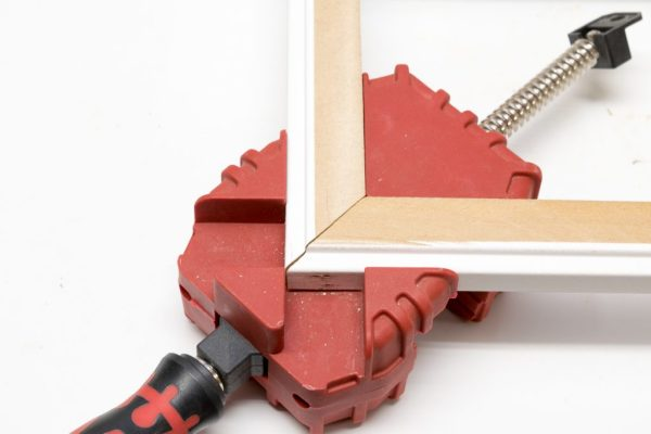 A corner clamp made it easier to hold the miter in place when using the nail gun.