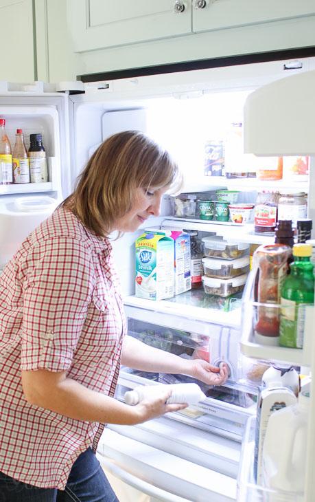 Woman replacing water filter in fridge