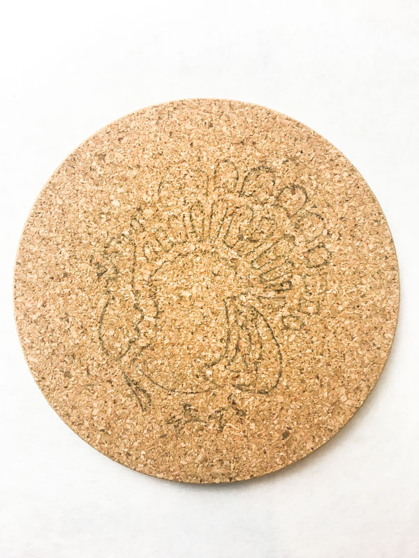 Remove the stencil to reveal your stenciled design on the cork trivets.