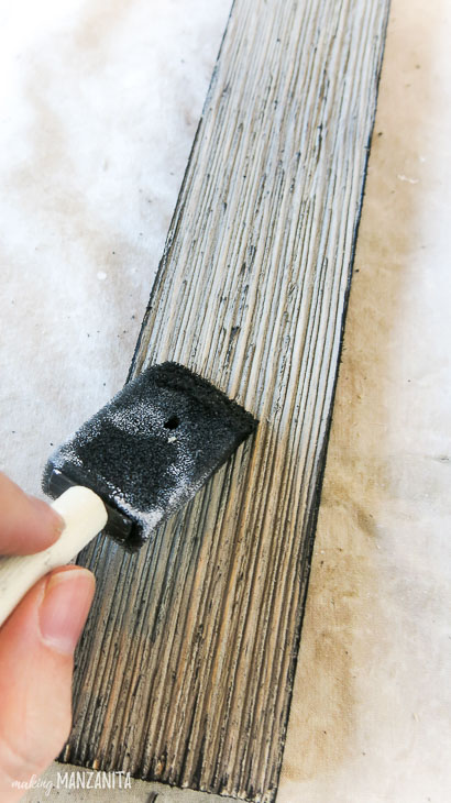 foam dry brushing black onto wood siding