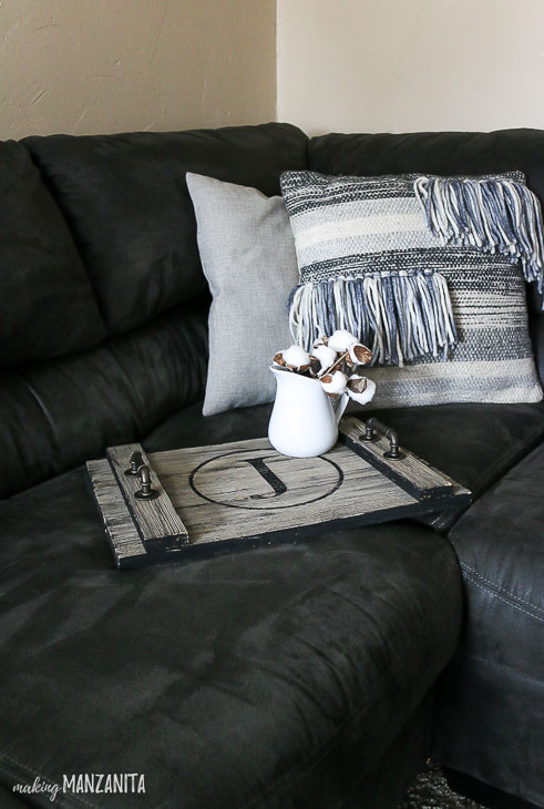 rustic wood serving tray on black couch, pillows in background