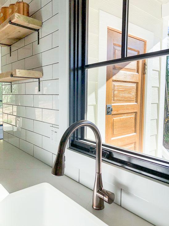 Plygem Mira black framed casement window over bronze faucet subway tile open shelving