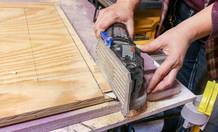 use Dremel Saw Max to cut groove in bottom of barn door