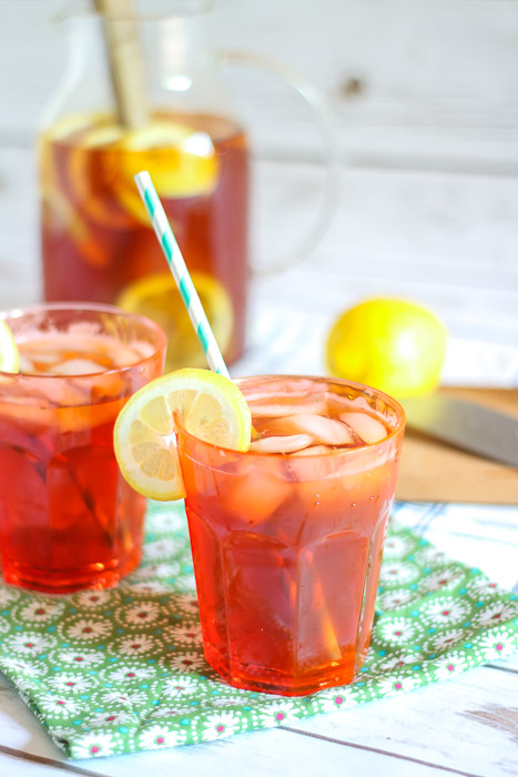 Closeup glass with sun tea and lemon slice with pitcher in background