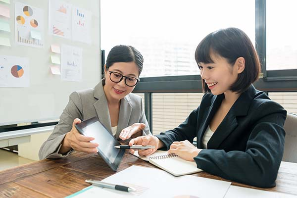 smiling elegant business woman using mobile pad computer showing cooperation document for her client and explaining new plan.