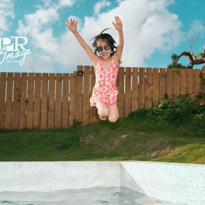 happy attractive little girl children playing in villa swimming pool and jumping into water to refreshing during summer season.