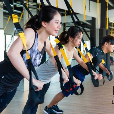 three happy Asian TRX learner enjoy training together and push up in a bright sunshine gym place.