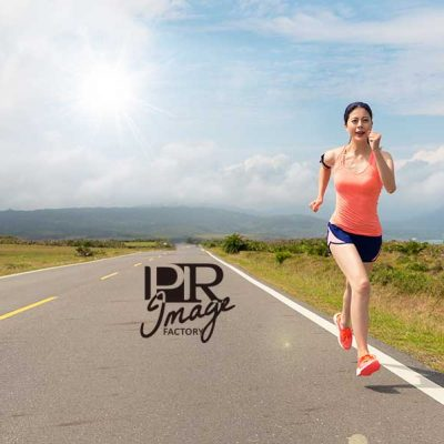 young beautiful woman happy running in the asphalt road movement while the leisure time of the holiday with sunny sky and attractive mountain views background over copyspace.