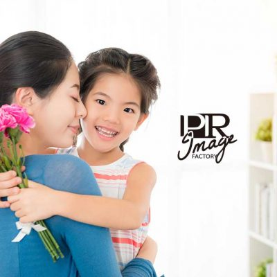 young mom embrace with little girl when she knowing her daughter was preparing pink carnations bouquets for mother's day gift in the living together.