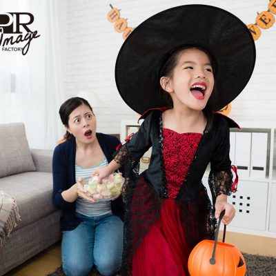 angry mom look at naughty happy child play trick or treat, grab sweets candy from her at home for halloween holiday