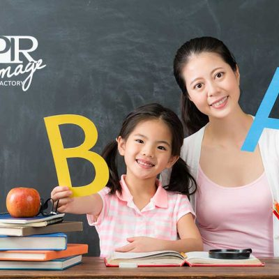 cute girl children with elegant young female teacher presenting english word looking at camera in chalkboard and showing back to school concept.