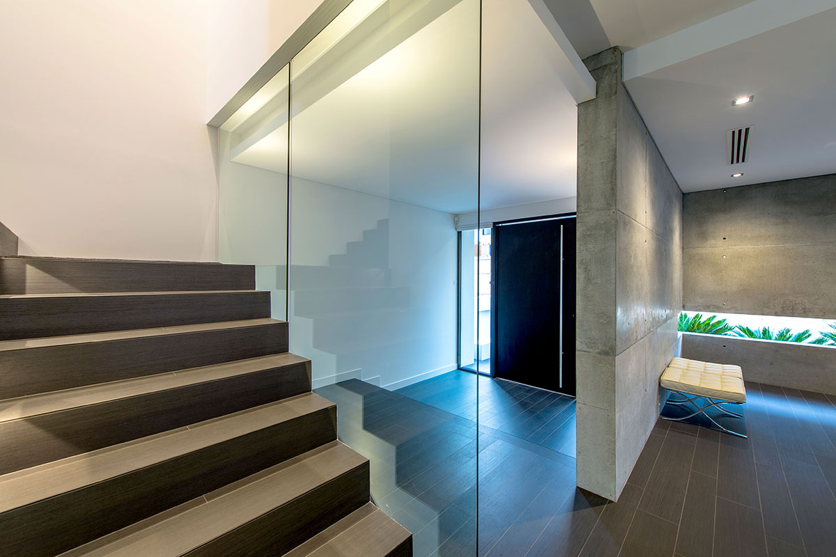 Private entrance way with floor to ceiling glass large timber doors are features in this custom built mosman park home