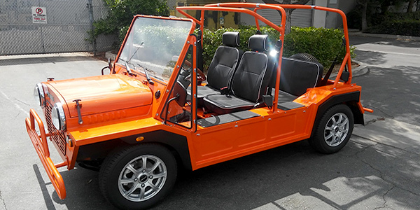 orange moke golf car with black seats and white piping
