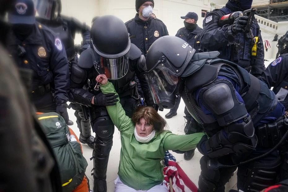 Una mujer es ayudada por la Policía durante la manifestación en el Capitolio.