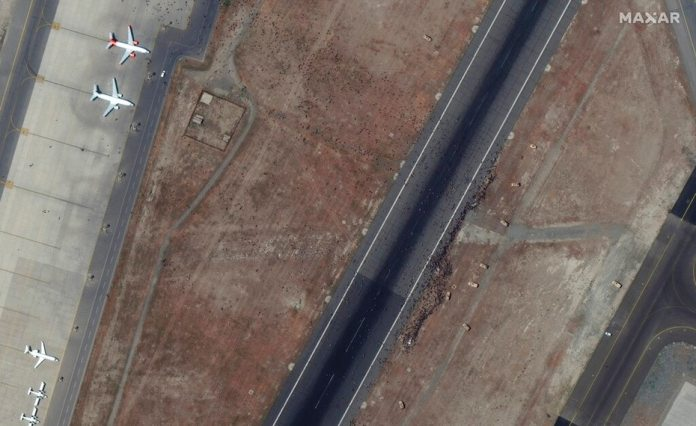 Satellite image of Maxar Technologies showing swarms of people on the runway of Kabul International Airport on August 16, 2021.