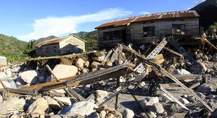 Mangled metal is seen in front of the homes of Kilembe copper mines workers destroyed by floods in Kasese district