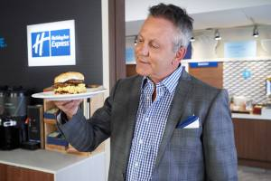 "Doug Gilmour with ""The Gloves Off Breakfast Sandwich,"" a biscuit topped with strawberry jam, a sausage patty, scrambled eggs and cream cheese."