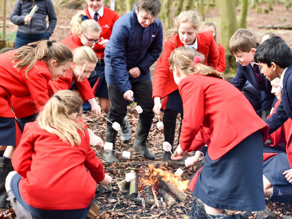 Kids in red blazers and navy coats stood around a campfire with marshmallows on sticks