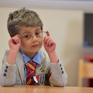 A young school boy dressed up as an old man with glasses, wearing a suit and tie.