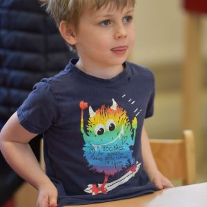 A young boy wearing a t-shirt that has a multi-coloured monster riding a skateboard.