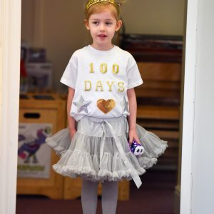 A young red haired girl dressed as a princess, with a gold tiara and tutu.