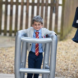 A small child dressed up as an old man, walking with an inflatable zimmer frame.