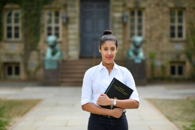 Avanthi Cole holding her senior thesis in front of Nassau Hall