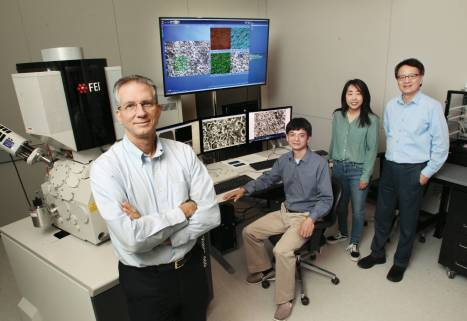 Researchers sit and stand infront of a large display