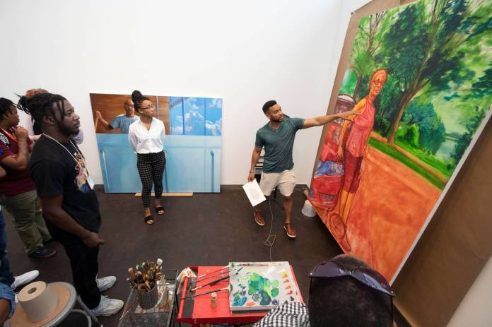 Painter Mario Moore points at a large unfinished painting on a tour of his studio
