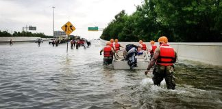 A photo of National Guard members helping people on a flooded highway overpass.
