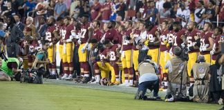 A photo of football players taking a knee during the National Anthem.