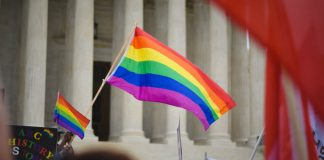 A photo of a rainbow flag being waved outside the U.S. Supreme Court.