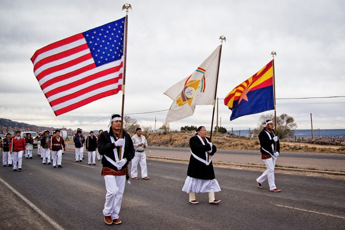 A photo of Native Americans marching along a highway with flags.