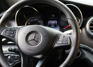 A photo of the steering wheel of a Mercedes car.