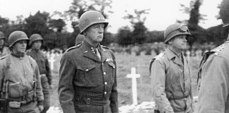 A black-and-white photo of George Patton marching through a cemetery.