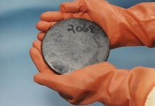 Two gloved hands holding a circular plate of uranium.