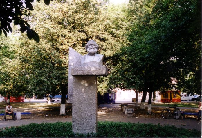 Photo of Karl Marx bust on a plinth in a small park