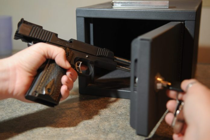 Image of a person putting a handgun into a gun safe.
