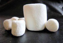 photograph of several marshmallows, the largest in the center standing upright
