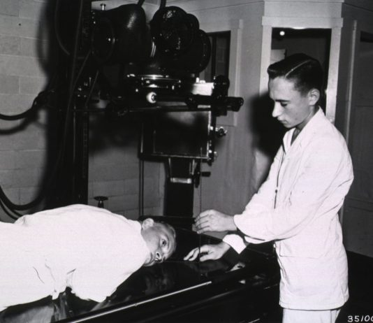 Black and white photograph of a medical student examining a person on a table