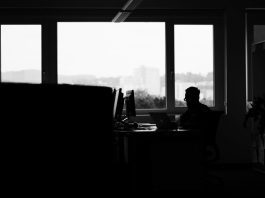 Image of a man alone in a dark computer room