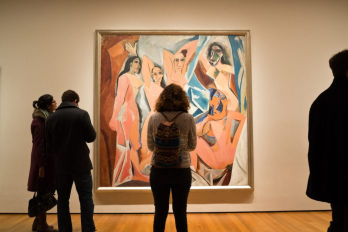 Silhouettes of people in front of Picasso's painting