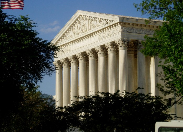 Photograph of the US Supreme Court framed by shrubbery