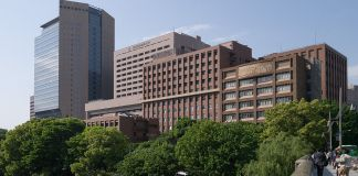 Slightly angled view of the exterior of a large complex of buildings known as the Tokyo Medical and Dental University with a stand of trees in front