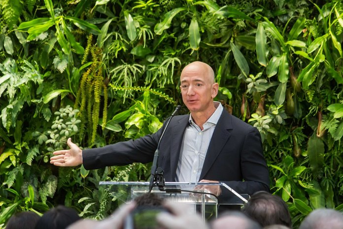 Photograph of Jeff Bezos speaking at a podium and gesturing with arm