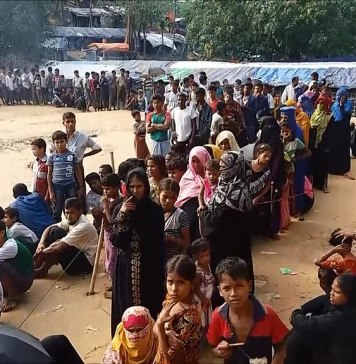 Photograph of a long line of people in a refugee camp