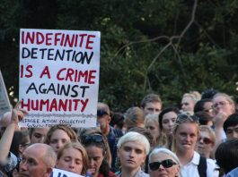 "Photograph of a rally with a person holding a sign saying ""Indefinite Detention is a crime against humanity"""