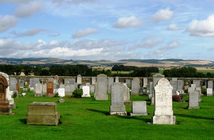 Photograph of a graveyard overlooking hills and plains