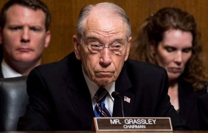 Image of Sen. Grassley with two people behind him