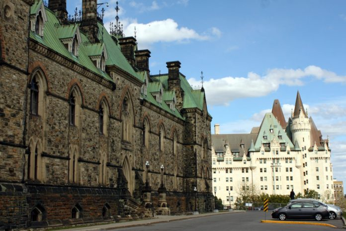 Photograph of the Canadian Parliament building in Ottawa with a hotel in the background